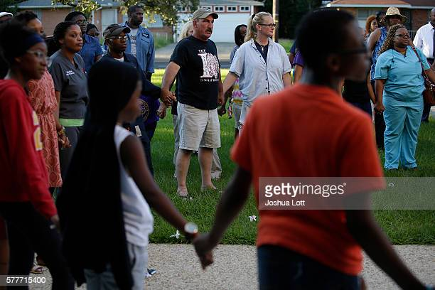 Mourners hold hands during candle light vigil for Baton Rouge Police Officer Montrell Jackson outside Istrouma High School July 19 2016 in Baton...