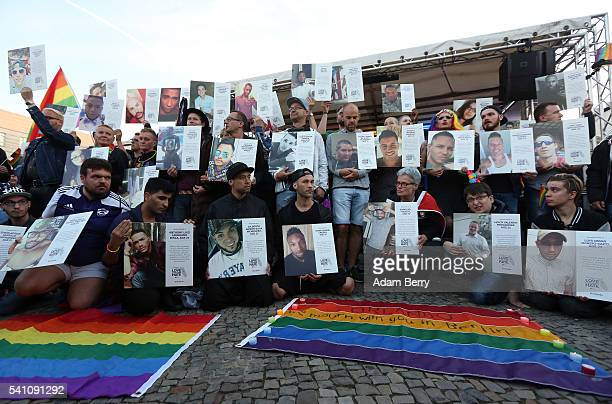 Mourners hold photographs of victims of a shooting at a gay nightclub in Orlando Florida nearly a week earlier during a vigil in front of the United...