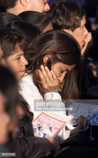 Mourners hold rosary beads and programs as they grieve during a prayer service for victims of the crash of American Airlines Flight 587 at Jacob Riis...