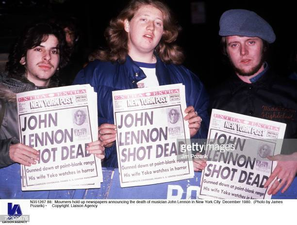Mourners hold up newspapers announcing the death of musician John Lennon in New York City December 1980