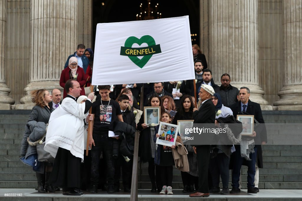 Mourners hold up photogrpahs of victims as they leave the Grenfell Tower National Memorial service at St Paul's cathedral on December 14, 2017 in London, England. The Royal Family and Prime Minister will join survivors of the Grenfell Tower fire at the memorial at St Paul's Cathedral for the six-month anniversary which killed 71 people. About 1,500 people are expected to attend the multi-faith service.
