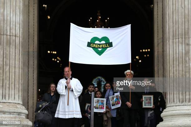 Mourners hold up photogrpahs of victims as they leave the Grenfell Tower National Memorial service at St Paul's cathedral on December 14 2017 in...