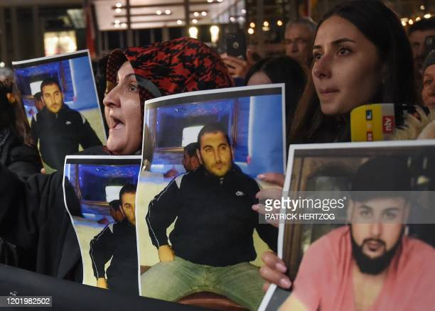 Mourners hold up photos believed to be of vicitims during a vigil close to a crime scene in Hanau near Frankfurt am Main western Germany on February...
