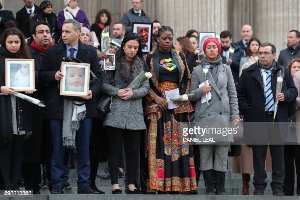 Mourners hold up photos of victims as they leave St Paul's cathedral after attending a Grenfell Tower National Memorial service on December 14 2017...