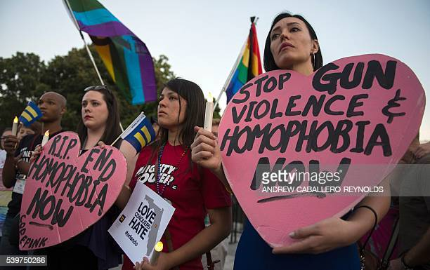 TOPSHOT Mourners hold up signs during a vigil in Washington DC on June 12 in reaction to the mass shooting at a gay nightclub in Orlando Florida...