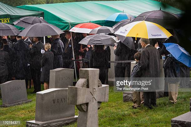 Mourners huddled under the shelter of their umbrellas as Senator Frank R Lautenberg during a burial service at Arlington National Cemetery in...