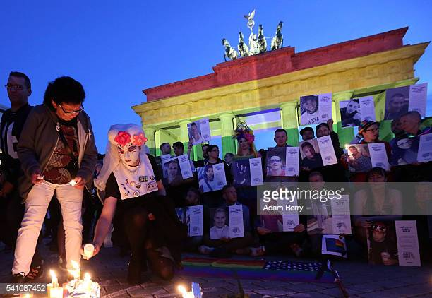 Mourners in front of a LGBT rainbow flag at Brandenburg Gate light memorial candles as others stand with photographs of victims of a shooting at gay...