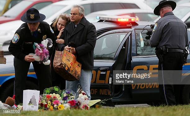 Mourners including a Newtown Police officers gather at a makeshift memorial outside St Rose of Lima Roman Catholic Church during the first day of...