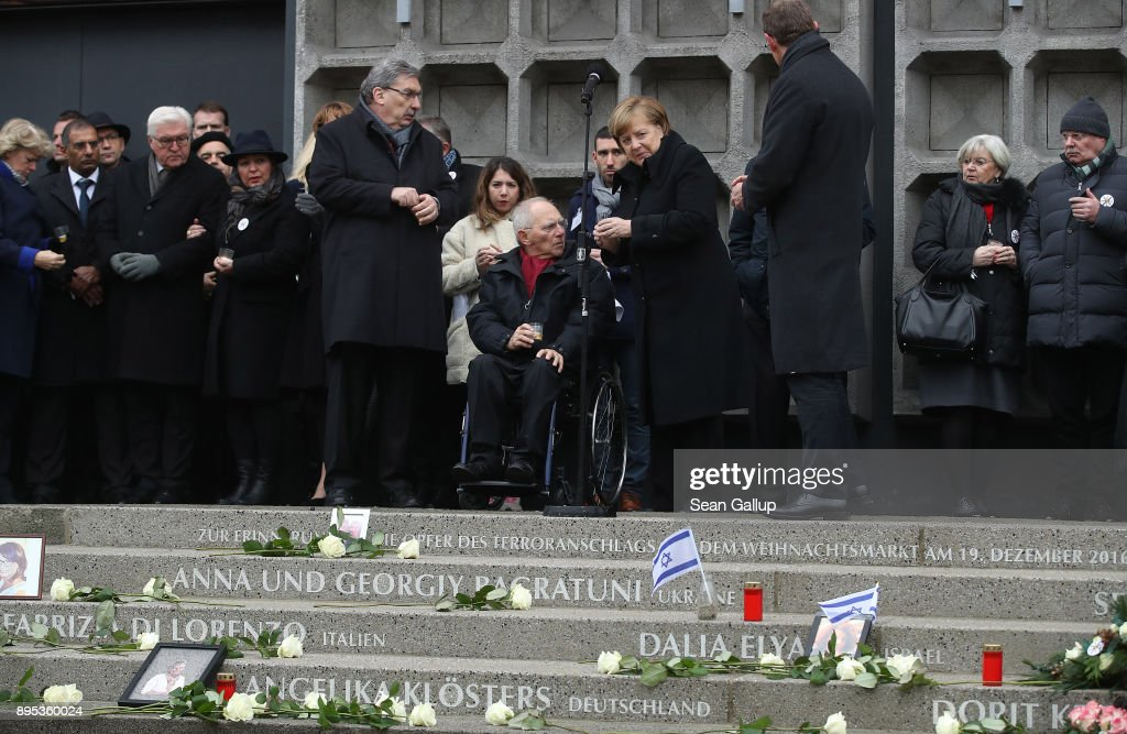 Mourners, including German Chancellor Angela Merkel (C-R) and Bundetag President Wolfgang Schaeuble (C-L), prepare to lay candles following the inauguration of a memorial to victims at the site of the 2016 Christmas market terror attack at Breitscheidplatz on the attack's first anniversary on December 19, 2017 in Berlin, Germany. On December 19, 2016, Tunisian immigrant Anis Amri hijacked a truck after killing the driver and plowed it into the Christmas market, killing 11 people and injuring 56 in an Islamist-motivated plot. Victims and their relatives met with Chancellor Merkel yesterday after expressing their frustration against what they feel has been an inadequate response by the German government to the victims' trauma.