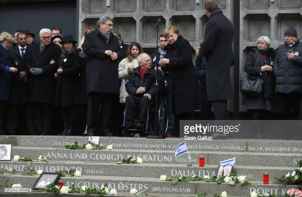Mourners including German Chancellor Angela Merkel and Bundetag President Wolfgang Schaeuble prepare to lay candles following the inauguration of a...
