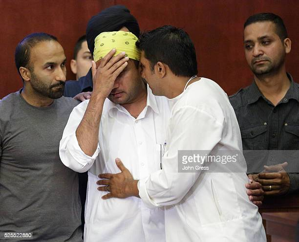 Mourners including Harpreet Singh and Amardeep Kaleka who's father Temple President Satwant Kaleka was killed cry during a press conference in Oak...