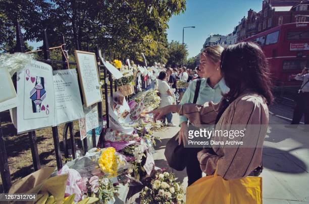 Mourners inspecting floral tributes and messages of condolence in memory of British Royal Diana Princess of Wales on the railings outside Kensington...