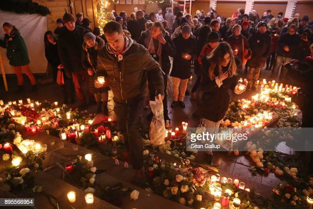 Mourners lay candles at a memorial to victims following the memorial's inauguration at the site of the 2016 Christmas market terror attack at...