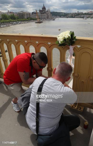 Mourners lay flowers and candles on the bridge over the Danube on May 31 2019 in Budapest near the spot of a boat accident with seven dead and 21...
