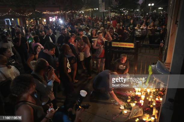 Mourners leave flowers and candles at the entrance of Ned Peppers bar in the Oregon District following a memorial service to recognize the victims of...
