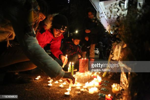 Mourners light candles and place flowers as they attend a vigil for the victims of a plane crash in Iran outside Amir Bakery on Lonsdale ave in North...