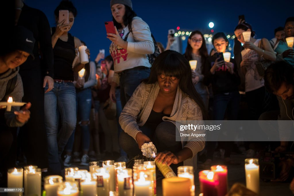 Mourners light candles during a vigil at the corner of Sahara Avenue and Las Vegas Boulevard for the victims of Sunday night's mass shooting, October 2, 2017 in Las Vegas, Nevada. Late Sunday night, a lone gunman killed more than 50 people and injured more than 500 people after he opened fire on a large crowd at the Route 91 Harvest Festival, a three-day country music festival. The massacre is one of the deadliest mass shooting events in U.S. history.