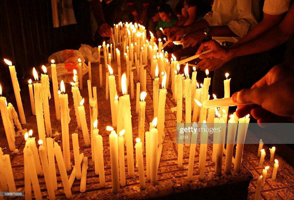 Mourners light candles during a vigil fo