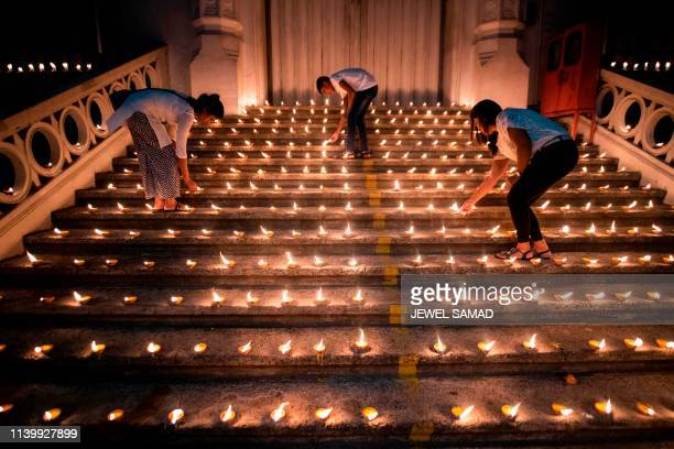 TOPSHOT Mourners light candles during a vigil in memory of the bomb blast victims in Colombo on April 28 a week after a series of bomb blasts...