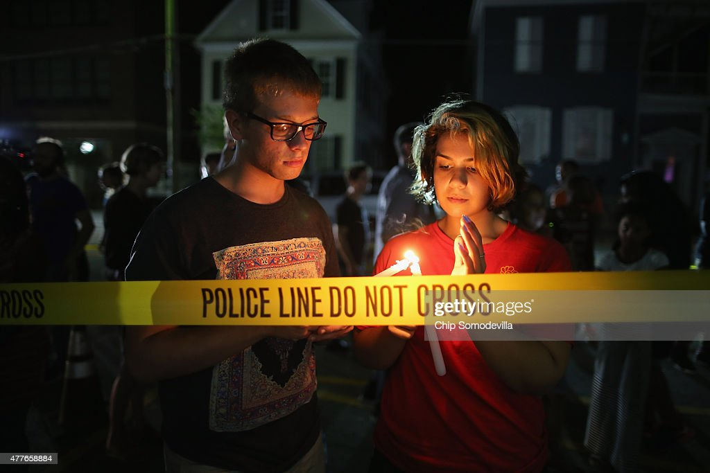 Mourners light candles for the nine victims of last night's shooting at the historic Emanuel African Methodist Episcopal Church June 18, 2015 in Charleston, South Carolina. Dylann Storm Roof, 21, of Lexington, South Carolina, who allegedly attended a prayer meeting at the church for an hour before opening fire and killing three men and six women, was arrested today. Among the dead is the Rev. Clementa Pinckney, a state senator and a pastor at Emanuel AME, the oldest black congregation in America south of Baltimore, according to the National Park Service.