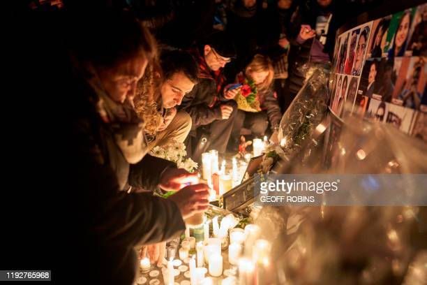 TOPSHOT Mourners light candles for the victims of Ukrainian Airlines flight 752 which crashed in Iran during a vigil at Mel Lastman Square in Toronto...