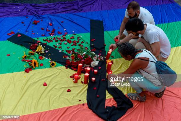 TOPSHOT Mourners light candles placed on rainbow flag draped with a black crape outside Barcelona's city hall during a vigil at Sant Jaume Square in...
