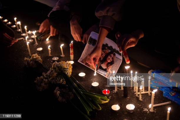 Mourners light candles while gathering during a vigil for the victims of the Ukraine International Airlines flight that was unintentionally shot down...