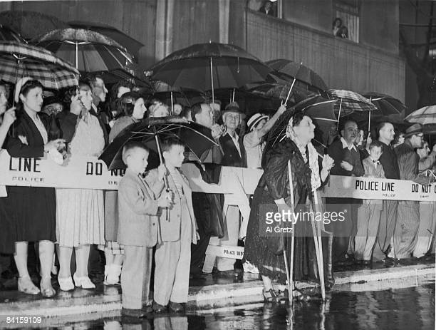 Mourners line the street in the rain to watch the funeral morocade in honor of American baseball player Babe Ruth as it travels along the crowdlined...