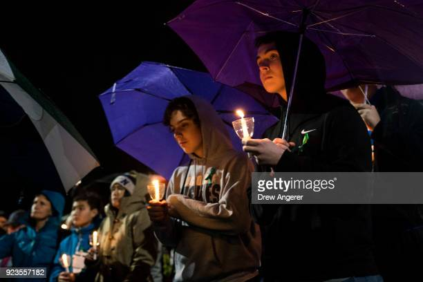 Mourners listen while names are read aloud during a community vigil at Newtown High School for the victims of last week's mass shooting at Marjory...