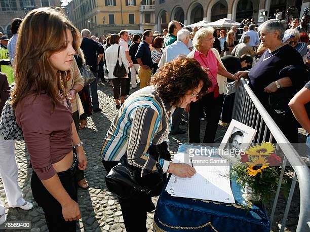 Mourners look at a book of condolences prior to the funeral of Luciano Pavarotti on September 8 2007 in Modena Italy