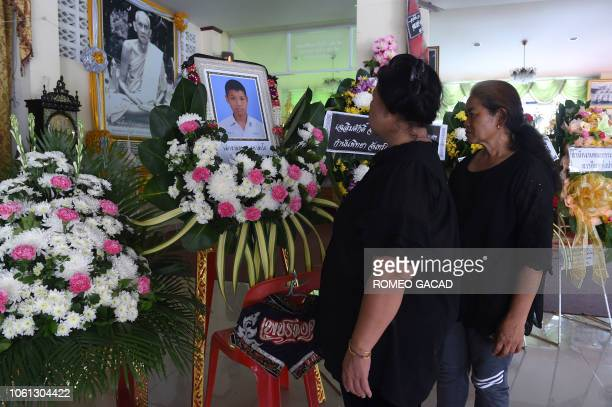 Mourners look at a portrait of 13yearold Muay Thai boxer Anucha Tasako next to his coffin during a funeral at a Buddhist temple in Samut Prakan...