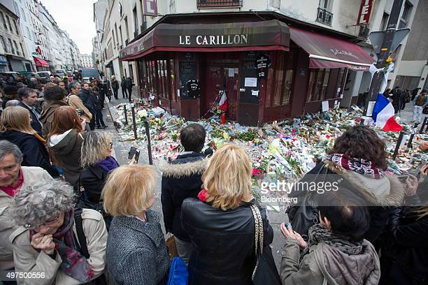 Mourners look at flowers at the Le Carillon restaurant the site of one of Friday's terror attacks in Paris France on Monday Nov 16 2015 Monday marked...