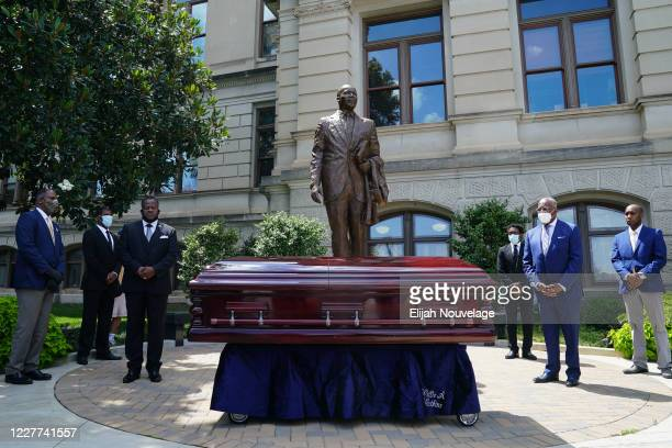 Mourners look on as the body of civil rights leader C.T. Vivian rests in front of a statue of Dr. Martin Luther King Jr. At the Georgia Capitol...