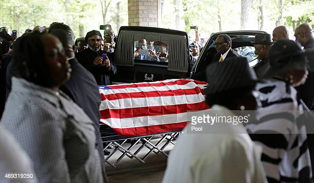 Mourners look on as the casket of Walter Scott is removed from a hearse for his funeral at WORD Ministries Christian Center April 11 2015 in...
