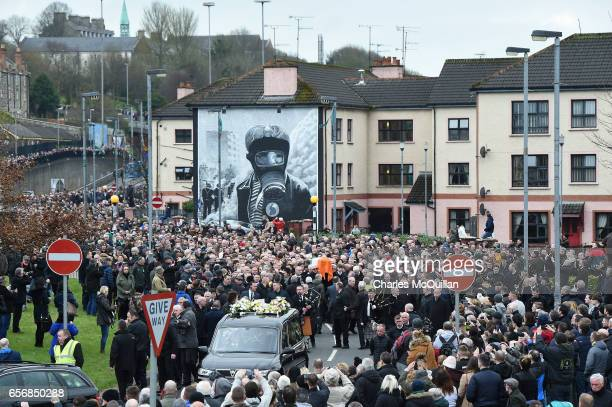 Mourners look on as the funeral cortege passes through Free Derry Corner on March 23 2017 in Londonderry Northern Ireland The funeral is held for...