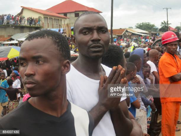 Mourners look on as victims of a mudslide are buried at the Paloko Cemetery in Waterloo on August 17 2017 Sierra Leone buried at least 300 victims of...