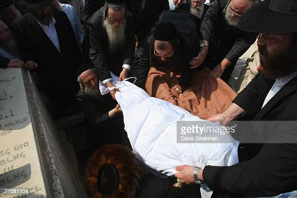 Mourners lower the shroudwrapped body of Rabbi Avraham Shapira into his grave during his funeral September 28 2007 on the Mt of Olives in Jerusalem...