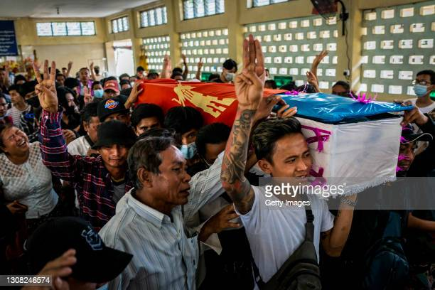 Mourners make three-fingered salutes while carrying a coffin during the funeral of Aung Kaung Htet who was killed when military junta forces opened...