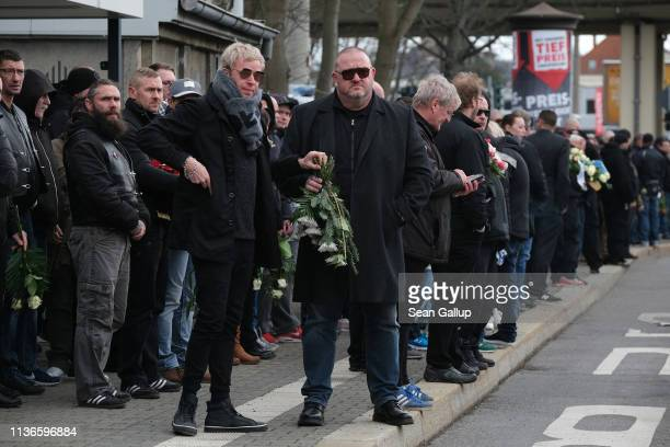 Mourners many of them from the Chemnitz football hooligan scene wait outside Michaelis cemetery for the arrival of the hearse carrying the coffin of...
