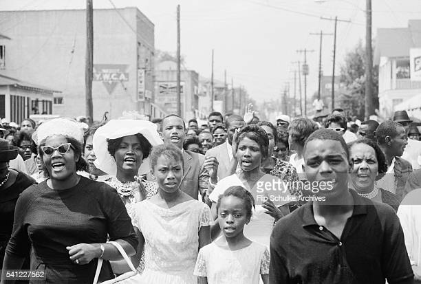 Mourners march and sing through Jackson Mississippi in a funeral procession for slain civil rights leader Medgar Evers