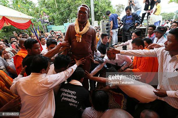 Mourners move a statue of prominent political analyst Kem Ley to a ceremonial place for a funeral ceremony to mark 100 days since his death after the...