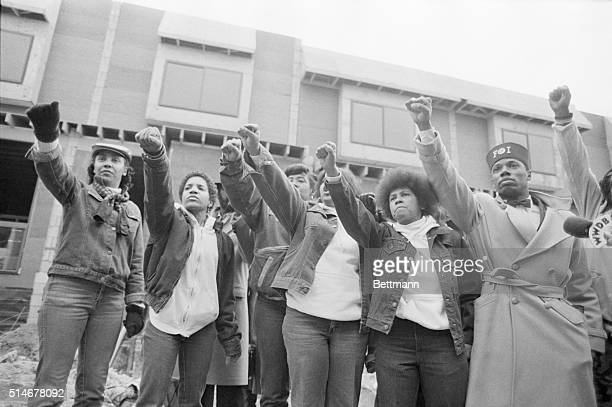 Mourners of MOVE members killed in the bombing by the Philadelphia Police stand in front of their former headquarters. They raise their arms with the...