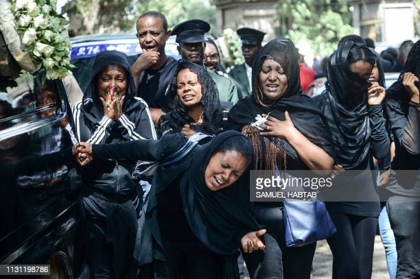 TOPSHOT Mourners of victims of the crashed accident of Ethiopian Airlines react beside a funeral car during the mass funeral at Holy Trinity...