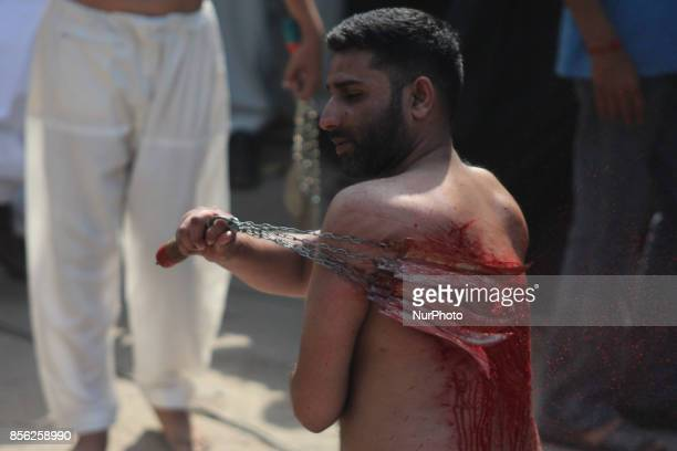 Mourners oozing themselves with knives and chains to express their devotion during the 10th Muharram Ashura Procession of Muharram ul Harram in...