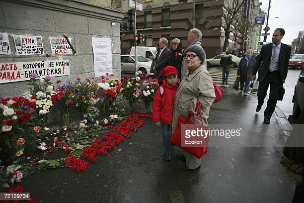 mourners pass flowers outside a house in central Moscow where investigative journalist Anna Poltkovskaya was killed October 7 on October 9 2006 in...