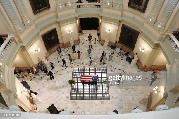 Mourners pay their respect at the flag-draped casket of Rep. John Lewis as he lays in repose at the Georgia State Capitol on July 29, 2020 in...