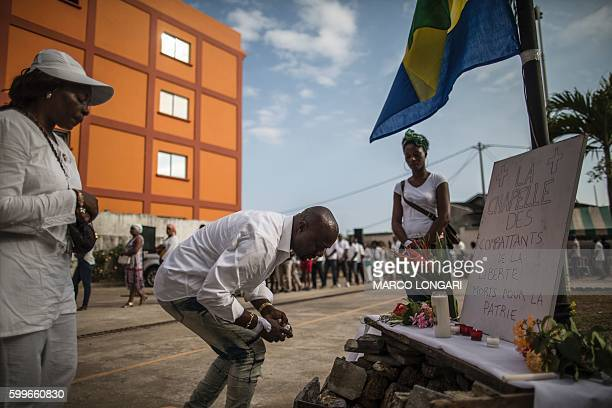 Mourners pay their respect by an improvised altar for those who perished during the post electoral violence in Libreville on September 6 2016 at the...