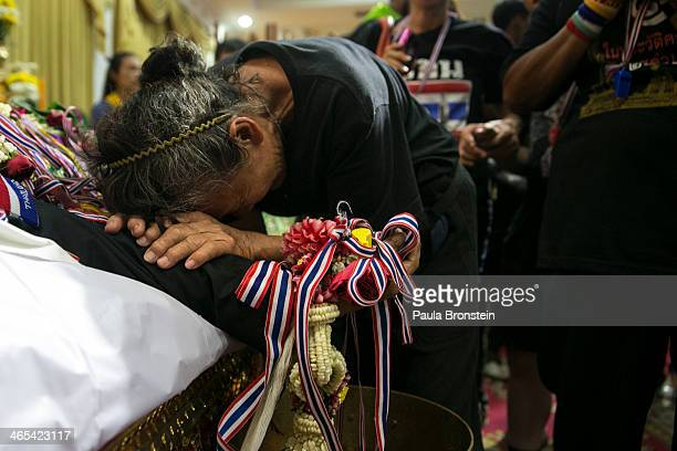 Mourners pay their respects over the body of Sutin Tharatin a core antigovernment leader who was killed by gunmen yesterday on January 27 2014 in...