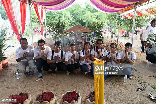 Mourners pay their respects to prominent political analyst Kem Ley in front of his grave during a funeral ceremony in Takeo province to mark 100 days...