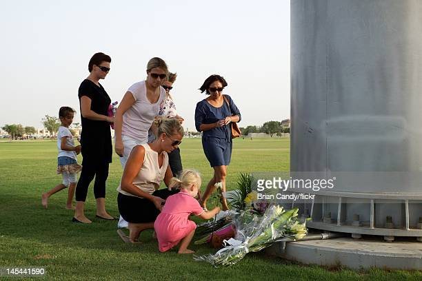 Mourners place floral tributes as they attend a vigil for the 19 victims of the Villaggio mall fire in Aspire Park on May 29 2012 in Doha Qatar 13 of...